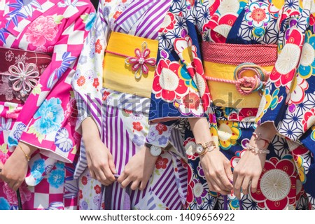 """Young girl wearing Japanese kimono standing in front of Sensoji Temple in Tokyo, Japan. Kimono is a Japanese traditional garment. The word """"kimono"""", which actually means a """"thing to wear""""  Royalty-Free Stock Photo #1409656922"""