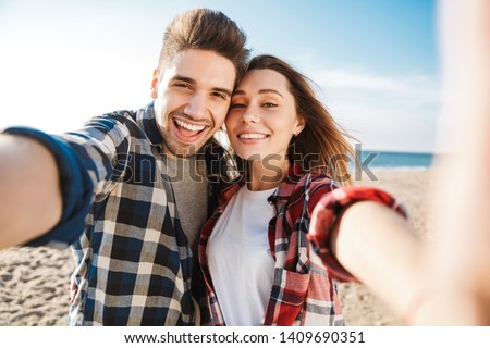Photo of happy young loving couple outside in free alternative vacation camping take selfie by camera.