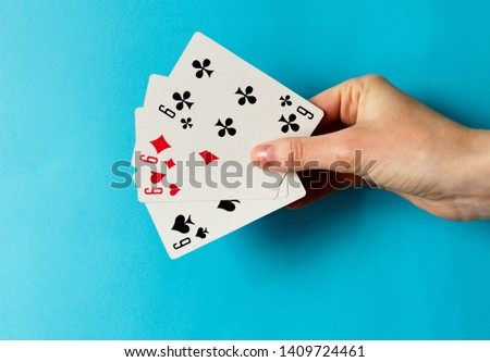 Playing cards in hand isolated on blue background. Space for text.  Playing cards isolated on blue background. Set of hearts, spades, clubs and diamonds ace. Concept for games.