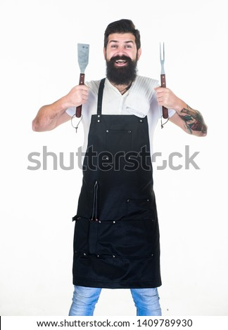 He is a great cook. Happy grill cook with cooking utensils. Bearded man holding fork and spatula for cooking and serving barbecue. Master cook wearing grilling apron. Chief cook in workwear. Cookout. #1409789930