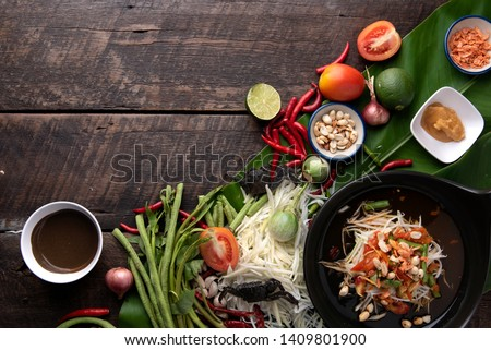 Som Tam Thai - Papaya Salad Thai Food Style on wooden table background. Thai Food Concept. Top View #1409801900