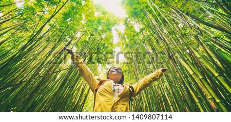 Sustainable eco-friendly travel tourist hiker walking in natural bamboo forest happy with arms up in the air enjoying healthy environment renewable resources. #1409807114