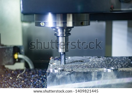 CNC milling machine during operation. Produced milling parts with a strong supply of cooling lubricants. #1409821445