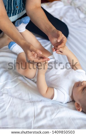 Newborn baby massage. Mom doing gymnastics with kid. Mommy massaging her cute baby boy. Moving a baby's legs, relieve constipation. Mother doing exercises and movements to stimulate a baby's bowels. #1409850503