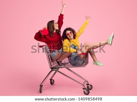 Side view of excited young friends smiling and raising hands while riding shopping trolley against pink background Royalty-Free Stock Photo #1409858498