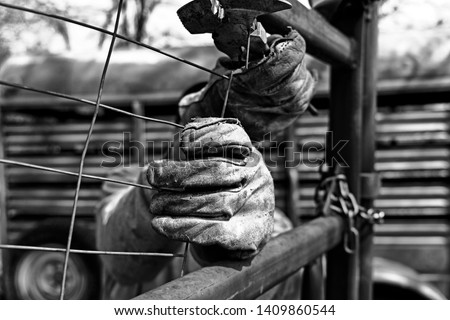 Vintage style hard work shows leather work gloves close up during fencing on farm, detail in rugged manual labor. Royalty-Free Stock Photo #1409860544