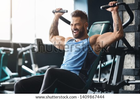 Chest exercise. Handsome muscular man working out hard at gym, free space #1409867444