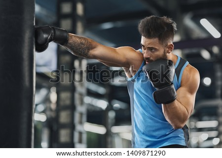 Young sportsman boxing workout at gym, guy punching boxing bag, free space #1409871290