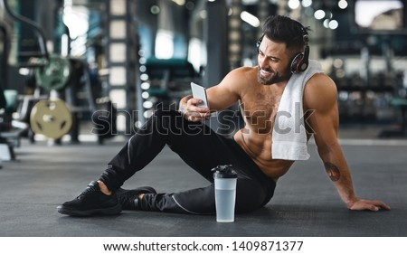 Online personal trainer on mobile phone. Muscular man using cellphone at gym, free space Royalty-Free Stock Photo #1409871377
