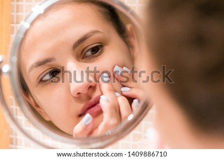 Young girl squeezes pimple on the fer face in front of a bathroom mirror. Beauty skincare and wellness morning concept. #1409886710