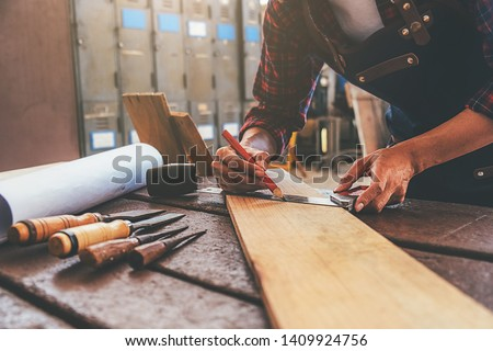 Carpenter working with equipment on wooden table in carpentry shop. woman works in a carpentry shop. #1409924756