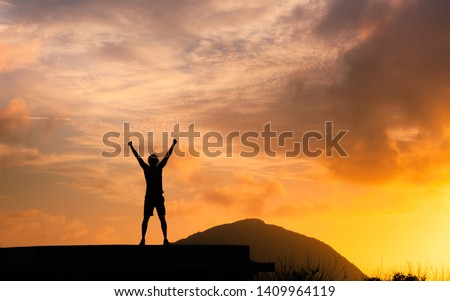 Strong man with fist in the air standing on top a mountain. Triumph, victory and feeling determined. #1409964119