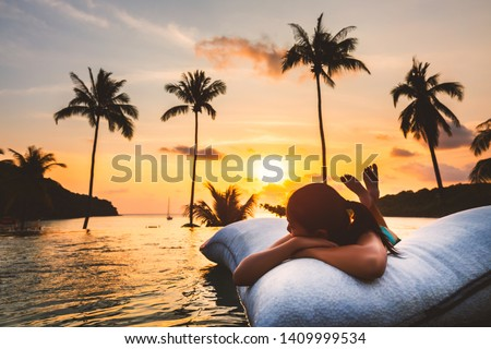 Summer vacation concept, Silhouette asian woman with bikini relax in infinity pool hotel resort with sea beach and palm tree background at sunset in Koh Kood, Thailand #1409999534