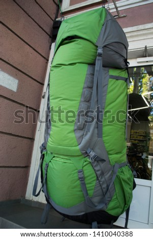 giant green backpack hanging in front of the door #1410040388