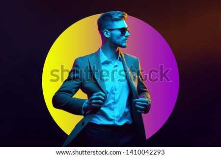 Young handsome model posing in a studio in a trendy neon light. Fashionable man in a stylish suit. Vibrant color. Bright colorful light effects. Disco style. Overlay. Gel filter. Supersaturated #1410042293