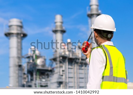 Engineer working at gas turbine electric power plant with talking on the walkie-talkie for controlling work