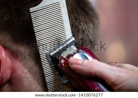 Close up of a male student having a haircut with hair clippers #1410076277