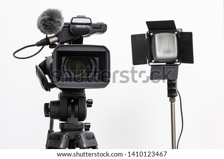 video camera on the tripod and spotlight harogen lamp isolated on white background, in concept of movie making equipment, TV production. #1410123467