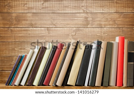 Old books on a wooden shelf. No labels, blank spine. #141016279