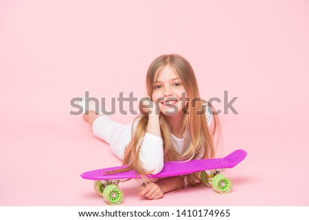 Kid adorable child long hair adore ride penny board. Happy childhood. Ride penny board and do tricks. Girl likes to ride skateboard. Active lifestyle. Girl having fun with penny board pink background. #1410174965