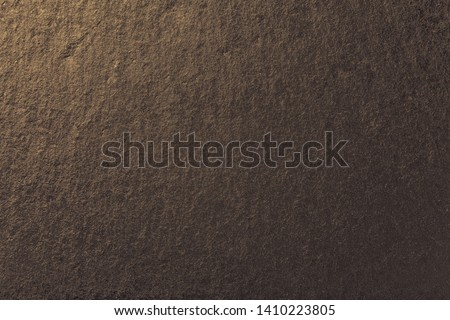 Dark bronze background of natural slate. Texture of brown stone closeup. Graphite golden backdrop macro #1410223805