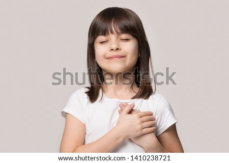 Little sincere adorable girl closed eyes holding hands on chest feeling gratitude pose isolated on sandy color beige background, arms on heart gesture of love appreciation gratitude, adoption concept #1410238721