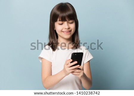 Little girl isolated on blue background hold smart phone look at screen smiling use internet online applications, play games, watch cartoons, parental control, children and modern tech usage concept