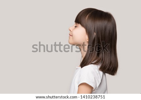 Profile side view face brown-haired little girl standing isolated on beige studio background, preschool kid do deep breath enjoy fresh air or dreaming fill with energy feeling healthy and good concept #1410238751