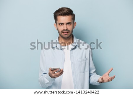 Isolated on blue background angry annoyed man frowns look at camera holding smart phone having problems with wi-fi no wireless connection, need repair broken phone, unpleasant message received concept #1410240422