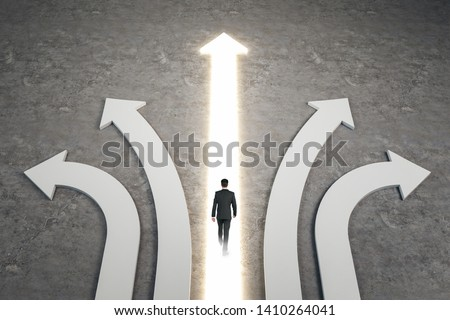 Businessman walking on abstract white and glowing arrows on concrete background. Different direction and success concept. #1410264041