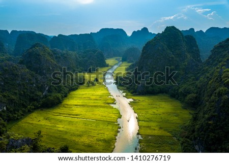 Aerial image of Tam Coc at harvest time. This is one of the most famous sightseeing in Vietnam where tourists cam cruise along a stream with nice paddy fields alongside.  #1410276719