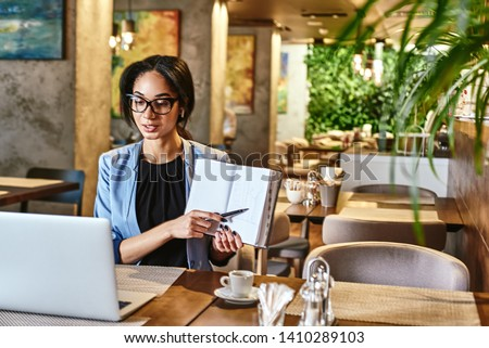 There are no secrets to success. It is the result of preparation, hard work, and learning from failure. Young businesswoman with headphones sitting in cafe in front of laptop and networking #1410289103