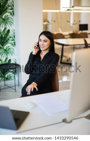 Woman working on laptop at office while talking on phone, backlit warm light #1410290546