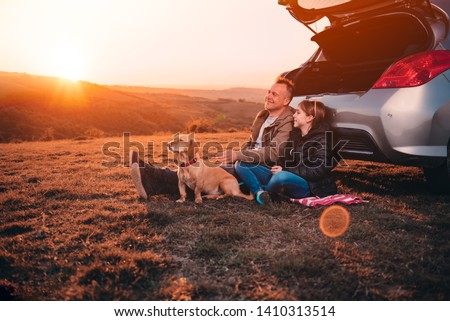 Father and daughter with small yellow dog camping on a hill while sitting on the ground by the car and having relaxing conversation #1410313514
