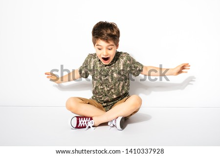 expressive little boy posing while sitting down on white background #1410337928