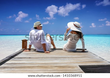A elegant traveler couple in white linen clothes sitting on a wooden jetty and enjoying their tropical holiday #1410368951