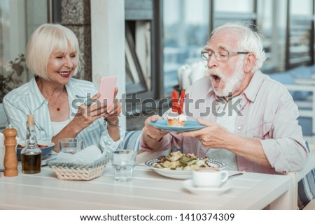 Funny moment. Emotional bearded man opening mouth while blowing candles on cake #1410374309