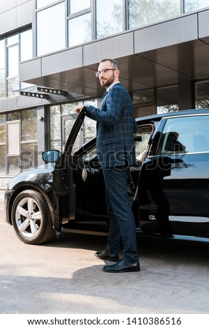 low angle view of businessman in suit standing near black car  #1410386516