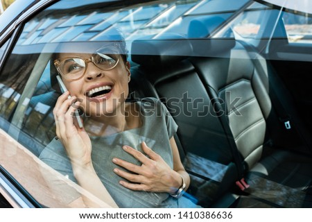 happy woman in glasses laughing while talking on smartphone in car  #1410386636