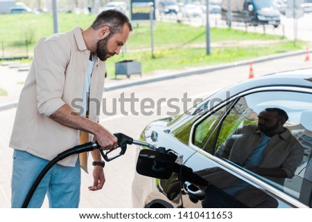 handsome man holding fuel pump and refueling black car at gas station  #1410411653