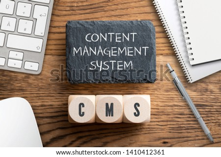 "acronym CMS on wooden cubes and writing slate with explanation ""Content Management System"" on wooden background #1410412361"
