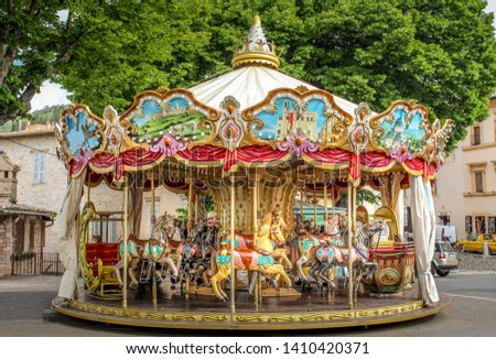 Colorful Carousel Attraction Ride With Wooden Horses in an Italian Village Royalty-Free Stock Photo #1410420371