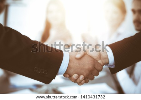 Business people shaking hands at meeting while theirs colleagues clapping and applauding. Group of unknown businessmen and women in modern white office. Success teamwork, partnership and handshake #1410431732