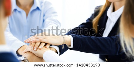 Business team showing unity with their hands together. Group of people joining hands and representing concept of friendship, teamwork and partnership #1410433190