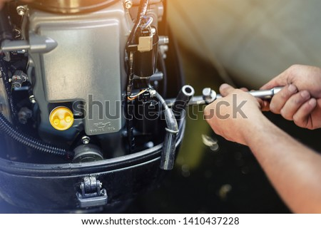 mechanic repairing inflatable motorboat engine at boat garage. Ship engine seasonal service and maintenance. Vessel motor with open cover #1410437228