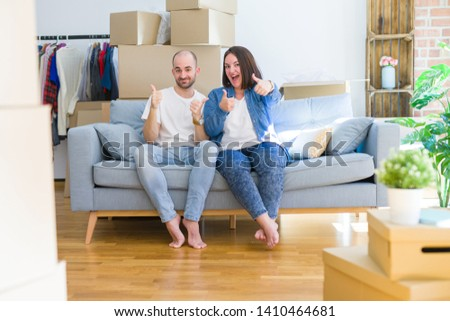 Young couple sitting on the sofa arround cardboard boxes moving to a new house success sign doing positive gesture with hand, thumbs up smiling and happy. Cheerful expression and winner gesture. #1410464681