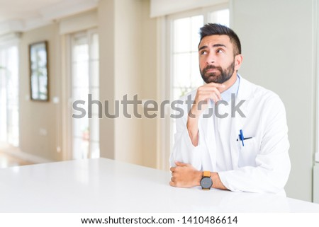 Handsome hispanic doctor or therapist man wearing medical coat at the clinic with hand on chin thinking about question, pensive expression. Smiling with thoughtful face. Doubt concept. #1410486614