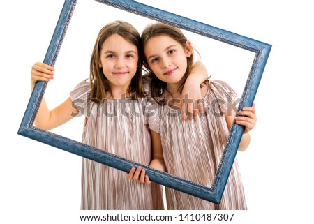 Identical twin girls are making happy expressions with picture frame. Children, sisters, girls posing in studio with picture frame, making different facial expressions. Family portrait, frontal view.