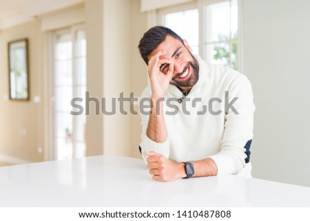 Handsome hispanic man wearing casual white sweater at home doing ok gesture with hand smiling, eye looking through fingers with happy face. #1410487808