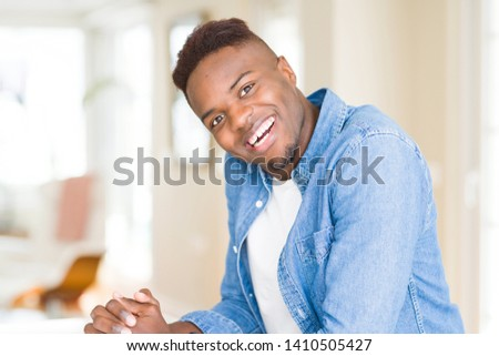 Handsome african young man smiling cheerful with a big smile on face #1410505427